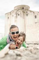 kaukasiska mamma och dotter kramar, ler foto