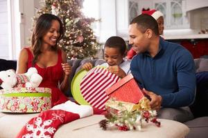 familj som öppnar julklappar hemma tillsammans