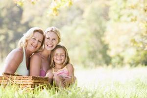 mormor med vuxen dotter och barnbarn på picknick foto