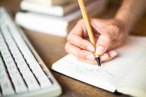 kvinnahänder skriver en penna i anteckningsboken foto