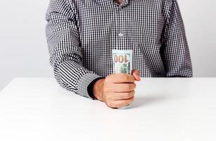 affärsman som håller sedlar vid skrivbordet foto