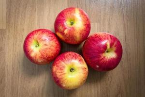 röda äpplen på träbakgrund foto