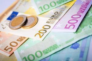 närbild av eurosedlar och mynt foto