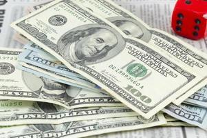 staplade dollarräkningar och en stor röd kub foto