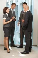 porträtt av unga kaukasiska affärsmän som pratar på kontoret foto