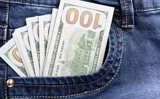pengar i fickan på blå jeans foto