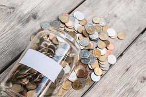 pengar burk med mynt på träbord, spara koncept foto