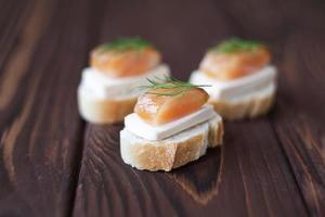 små smörgåsar med bearbetad ost och lax foto