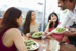 tre kvinnliga vänner njuter av lunch på takrestaurangen foto