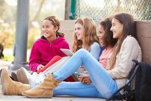 unga flickor som använder digitala surfplattor och mobiltelefoner i parken foto