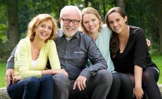 mamma far och två döttrar som ler utomhus
