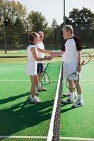 äldre och mogna vuxna skakar hand på tennisbanan