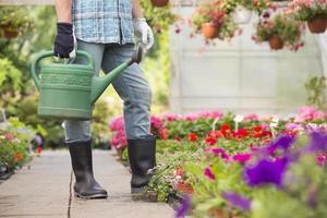 låg sektion av man som håller vattenkanna på växthus