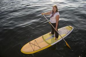 vacker kvinna paddling ombord foto
