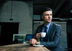 fundersam affärsman som dricker kaffe på café foto