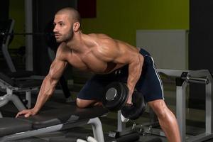 kroppsbyggare tränar tillbaka med hantel foto
