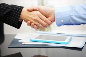 affärsman och affärskvinna handskakar över dokument och presentation