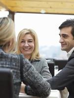 två kvinnor och en man i ett buinessmöte foto