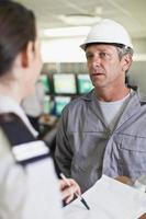 säkerhetspersonal pratar med arbetaren foto