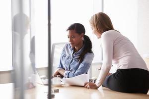 två tillfälligt klädda affärskvinnor som arbetar på kontoret foto