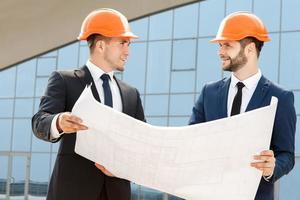 två ingenjörer som kontrollerar arkitektplanerna foto