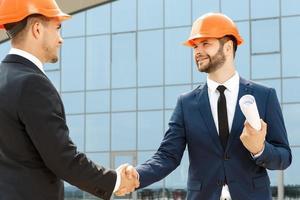 handskakning av två stiliga kollegor utomhus foto