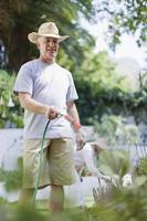 äldre man vattna växter i trädgården foto