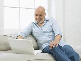 mogen man med bärbar dator på soffan foto