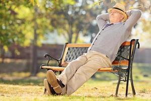avslappnad pensionär som sitter på bänken i parken foto