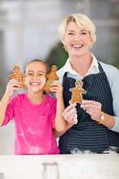 liten flicka och mormor som håller bara bakade pepparkakakakor foto