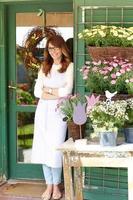 leende mogen kvinna blomsterhandlare på blomsteraffär foto