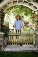 mogen kvinna som står under trädgårdsbågen, porträtt foto