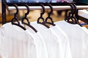 vita kläder som hänger på galgar i en butik foto