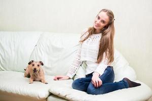vacker ung kvinna som sitter på soffan med en hund foto