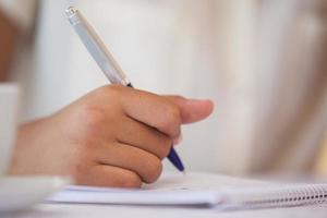 mitten av en affärskvinna som skriver i anteckningar foto