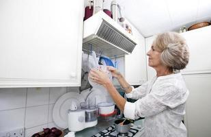 äldre kvinna hängande durkslag i inhemskt kök foto