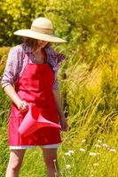 kvinna vattna växter i trädgården