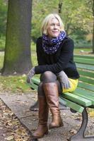kvinna sitter på en bänk foto