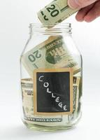 hand som sätter in pengar i att spara burk eller bank