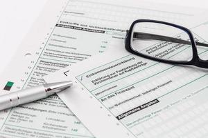 form av inkomstdeklaration med kulpenna och glasögon foto