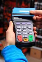 hand av kvinna som betalar med kontaktlöst kreditkort, nfc-teknik foto