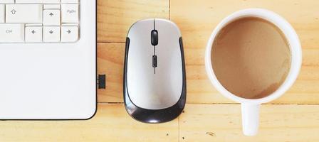 kaffe med vit anteckningsbok på träskrivbord. foto