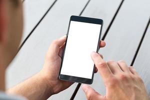 man håller smart mobiltelefon på träbord foto