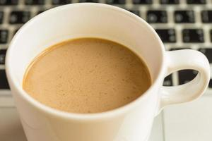 varm latte kaffekopp och bärbar dator på trä bakgrund och textur. foto