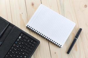 kontorsbord med anteckningsbok, penna och smartphone foto