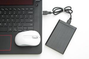 extern hårddisk ansluta till datorn anteckningsbok på vitt. foto