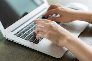 närbild av affärskvinna hand att skriva på laptop tangentbord foto