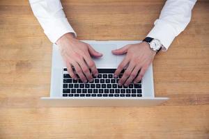 närbild bild av en affärsman händer med laptop foto