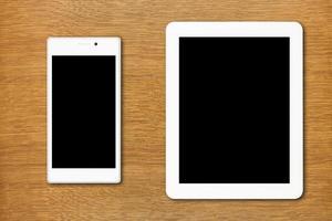 vit smartphone och surfplatta på bordet foto
