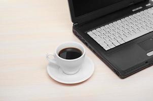 bärbar dator med färsk kopp kaffe och anteckningsbok foto